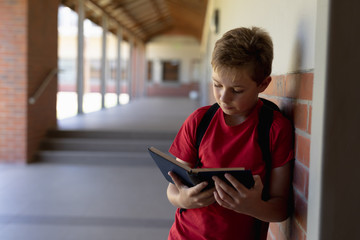 Schoolboy leaning against a wall in an outdoor corridor reading a book at elementary school