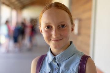 Schoolgirl standing in the schoolyard at elementary school