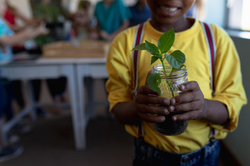 Schoolboy standing holding a seedling plant in a jar of earth in an elementary school classroom