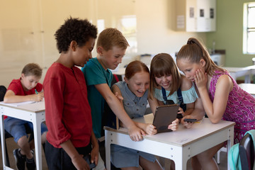 Group of schoolchildren around a desk using a tablet computer