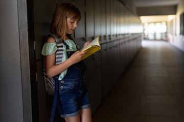 Schoolgirl leaning against a wall in an outdoor corridor reading a book at elementary school