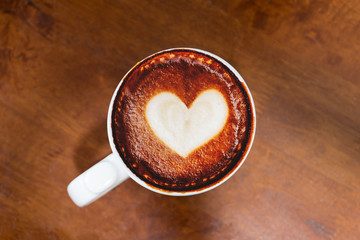 Coffee with love symbol on the top on wooden background. Flat lay shot. Copy space.