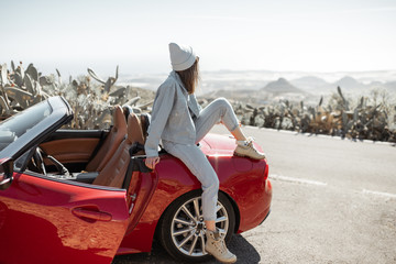 Lifestyle portrait of a stylish woman dressed casually in jeans and hat sitting on the car, enjoying road trip on the island