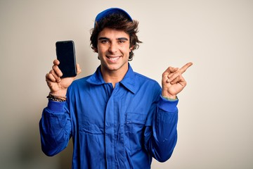 Young mechanic man wearing uniform holding smartphone over isolated white background very happy...