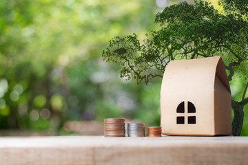 Property investment, Home loan, reverse mortgage concept. A small house model with stack of coins on wooden table with nature bokeh background.