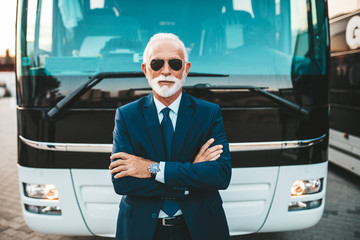 Mature beard bus driver standing in front of bus.