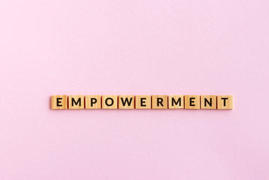Empowerment text wood blocks. Pink background.