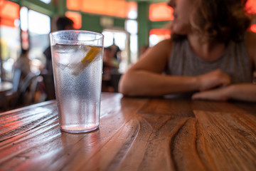 Glass of water with lemon and ice on restaurant table with woman