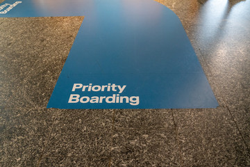Blue priority boarding lane painted on airport terminal floor leading to plane boarding