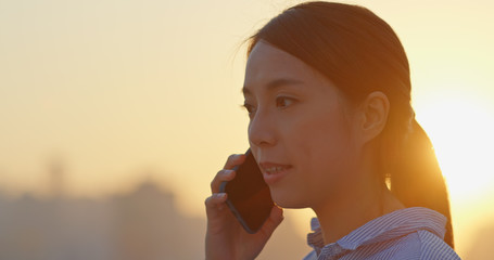 Wall Mural - Woman talk to mobile phone in city at sunset