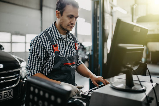 Portrait of happy male mechanic touching computer monitor in auto repair shop