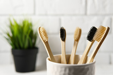 Close up of several biodegradable bamboo toothbrushes in a white glass on a brick wall background. Image with copy space, horizontal orientation. Zero waste concept.