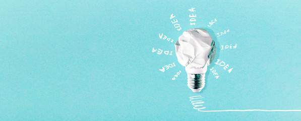 Wall Mural - crumpled white paper lightbulb with inscription idea on blue background, panoramic mock-up with space for text