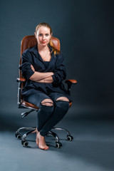 Beautiful blonde woman looking straight ahead, sitting in an armchair in a black shirt and black ripped jeans