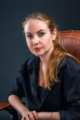 Beautiful blonde woman looking straight ahead, sitting in a chair in a black mantle