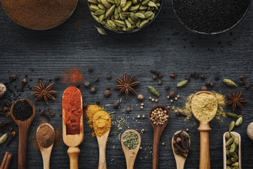 Various aromatic colorful spices and herbs in wooden spoons and scoops. Black ceramic bowls of seasonings. Ingredients for cooking.  Ayurveda treatments. Top view. Papier Peint
