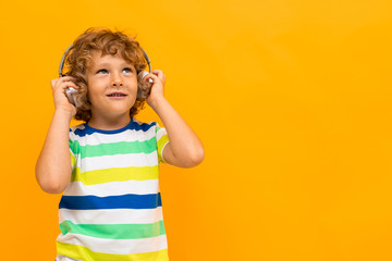 Little boy with curly hair in colourful t-shirt and shorts listen to music with big earphones...