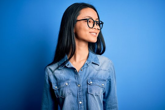 Young beautiful chinese woman wearing casual denim shirt over isolated blue background looking away to side with smile on face, natural expression. Laughing confident.