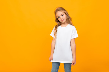 European cute girl in a white T-shirt with a mockup on a yellow background