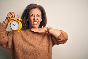 Middle age brunette woman holding clasic alarm clock over isolated background cutting throat with...