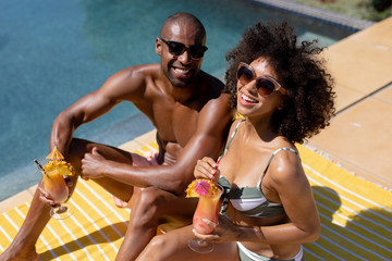 Young couple relaxing near swimming pool on a sunny day
