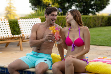 Happy young couple relaxing near the swimming pool