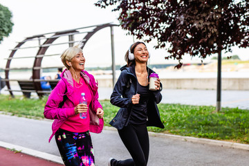 Happy mother and daughter jogging together outdoors in park.. Fotomurales