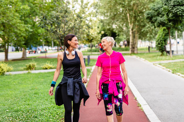 Obraz Happy mother and daughter enjoying in walk outdoors in park. - fototapety do salonu