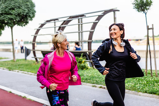 Happy mother and daughter jogging together outdoors in park..