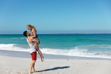 Boyfriend carrying girlfriend at the beach