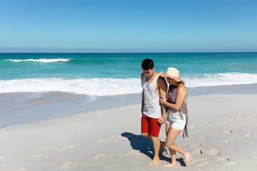 Young couple walking besides the beach