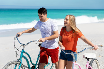 Young couple with bikes at the beach