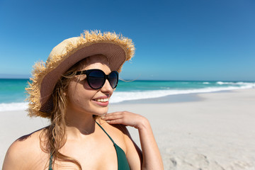 Young woman with hat smiling at the beach