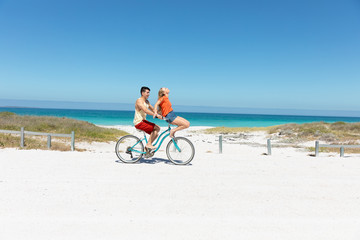 Young couple with bike at the beach