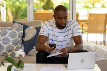 Young man using computer and mobile phone at home