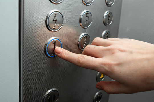 Female hand, finger presses the elevator button. up the career ladder.