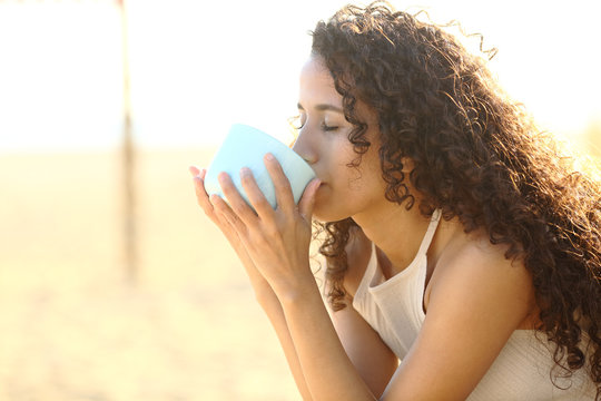 Latin girl drinking coffee on the beach