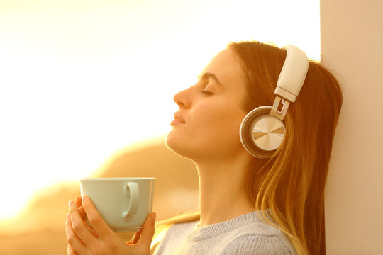 Relaxed woman listening to music with headphones