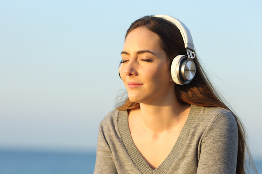 Woman with headphones relaxing listening to music