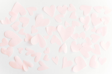 Happy valentines day. Cute pink pastel hearts on white paper  background. Flat lay. Pink paper heart cutouts on white backdrop, gentle image, greeting card. Valentine pattern