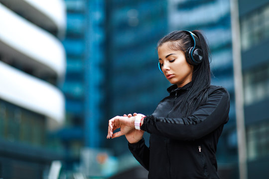 Young woman checking time at smartwatch after jogging in the city