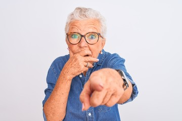 Senior grey-haired woman wearing denim shirt and glasses over isolated white background laughing at...