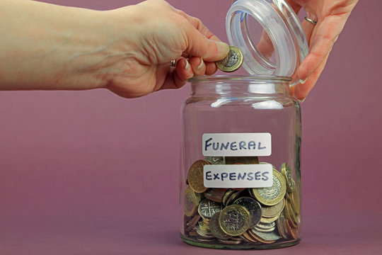 A hand adding a pound coin to a glass jar to pay for funeral expenses