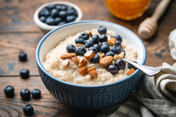 Photo sur Aluminium Pain Oatmeal porridge with blueberries, almonds in bowl on wooden table background. Healthy breakfast food
