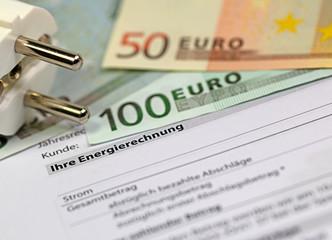 Energierechnung mit Geldscheinen und Netzstecker