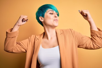 Young beautiful woman with blue fashion hair wearing casual jacket over yellow background showing...