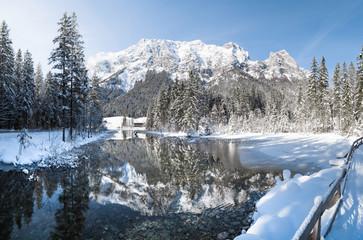 Idyllic winter wonderland with mountain lake in the Alps