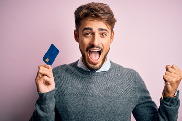 Young customer man with beard holding credit card for payment over pink background screaming proud and celebrating victory and success very excited, cheering emotion