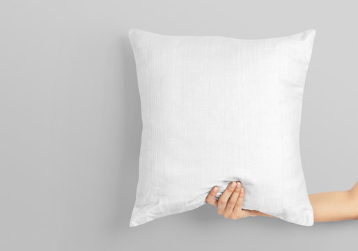 Woman hand holding white blank square pillow mockup on isolated background