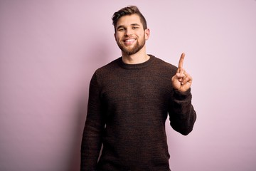 Young blond man with beard and blue eyes wearing casual sweater over pink background showing and pointing up with finger number one while smiling confident and happy. Fotomurales